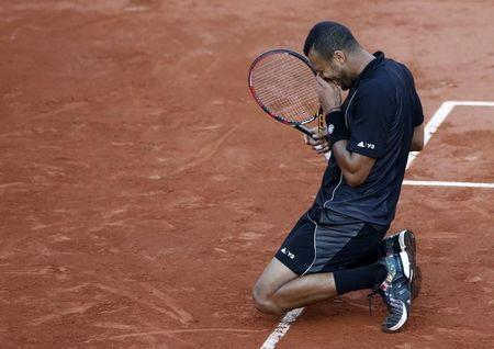 Jo-Wilfried Tsonga of France celebrates after defeating Kei Nishikori of Japan during their men's quarter-final match during the French Open tennis tournament at the Roland Garros stadium in Paris