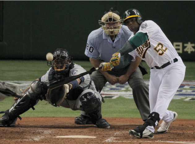 Oakland Athletics' Yoenis Cespedes hits a double as Seattle Mariners catcher Miguel Olivo looks on in the seventh inning of their American League season opening MLB baseball game at Tokyo Dome in Toky