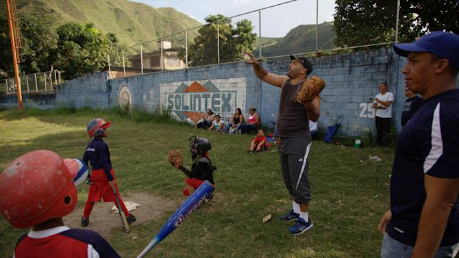 In this Oct. 25, 2012 photo, baseball coach Jorge Natera, center, directs his players during training at a baseball school in Maracay, Venezuela. Many of the boys are inspired by the example of Detroit Tigers slugger Miguel Cabrera, who learned the game on this very field. Their baseball school in the poor neighborhood where Cabrera grew up is one of many across Venezuela, a web for training young ballplayers that has made the country a powerhouse in the U.S. major leagues. (AP Photo/Ariana Cubillos)