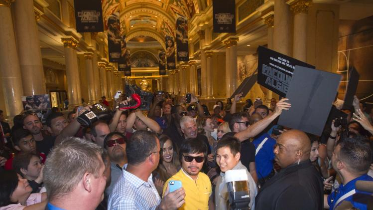 Boxer Manny Pacquiao takes a selfie with a fan as he arrives at the Venetian Las Vegas Resort in Nevada