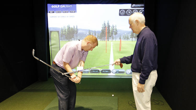 IMAGE DISTRIBUTED FOR GOLF GALAXY - Callaway club designer Roger Cleveland, right, instructs John Kollm, left, on short game techniques at Golf Galaxy's grand opening in Grapevine, Texas, on Friday, Nov. 9, 2012. (Brandon Wade/AP Images for Golf Galaxy)
