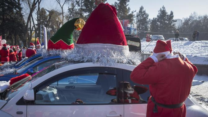 A reveler dressed as Father Frost, the equivalent of Santa Claus, adjusts his costume during a parade in Almaty
