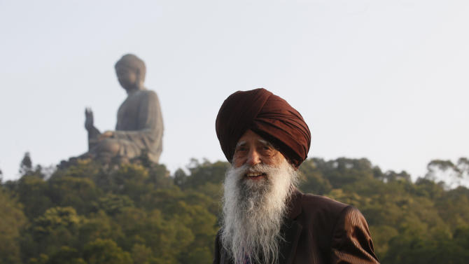 Centenarian marathon runner Fauja Singh, 101, originally from Beas Pind, India but now lives in London, visits the giant seated Buddha statue in Hong Kong's outlying Lantau Island Saturday, Feb. 23, 2013. Singh will participate in a 10-kilometer race at the Hong Kong Marathon on Sunday before retiring from public races.  (AP Photo/Kin Cheung)