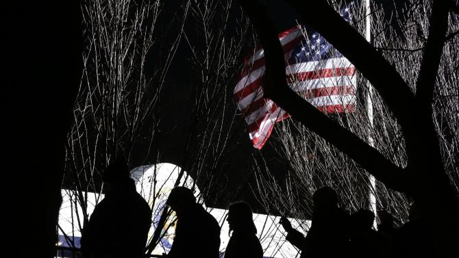 People watch the inaugural parade down Pennsylvania Avenue en route to the White House, Monday, Jan. 21, 2013, in Washington. Thousands  marched during the 57th Presidential Inauguration parade after the ceremonial swearing-in of President Barack Obama. (AP Photo/Frank Franklin II)