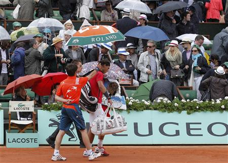 Nadal of Spain leaves the court under an umbrella as rain stops the play during his men's singles final match against Djokovic of Serbia at the French Open tennis tournament at the Roland Garros stadium in Paris
