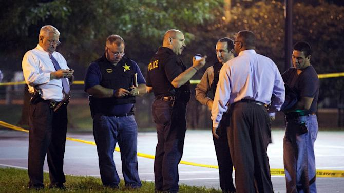 In this Thursday, Sept. 19, 2013, photo, officials convene near the scene of a shooting at Cornell Square Park in Chicago's Back of the Yard neighborhood that left multiple victims including a 3-year-old boy. Thursday night's attack was the latest violence in a city that has struggled to stop such shootings by increasing police patrols. (AP Photo/Sun-Times Media, Chandler West)