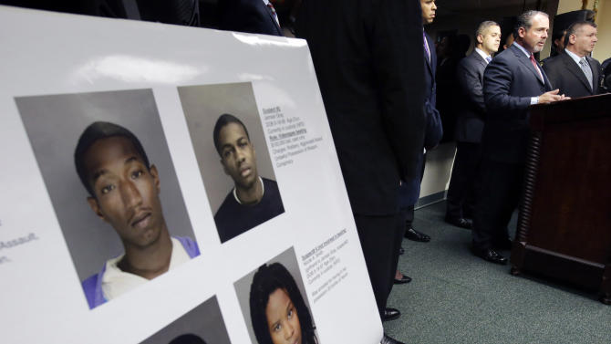 Newark Police Director Samuel DeMaio, second right at podium, stands near arrest photographs of three men and one woman after a video surfaced that showed a naked young man being whipped because of his father's debt during a news conference on Wednesday, Feb. 13, 2013.  They were identified as 22-year-old Ahmad Holt, 31-year-old Raheem Clark and 23-year-old Jamaar Gray. Police say Holt administered the beating, using a belt provided by Clark. Charges include robbery and aggravated assault.   The video shows a 21-year-old man being forced to strip and then whipped with a belt, supposedly because his father owed someone $20. Subsequent to the police investigation, Nicole A. Smith was arrested for drug possession. (AP Photo/Mel Evans)