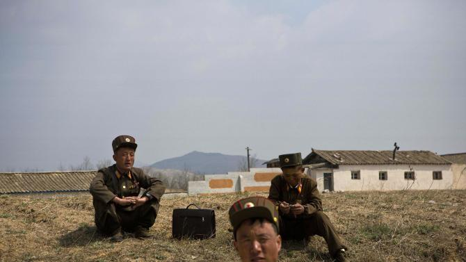 NKorean soldiers put down arms to help plant crops