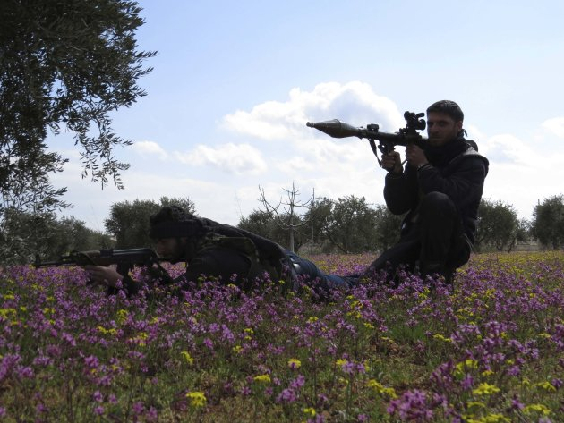 Free Syrian Army fighters hold their weapons and take positions in preparation for what they say is an ambush against forces loyal to Syria's President Bashar al-Assad in Binnish in Idlib Province