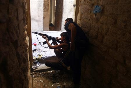 Ahmad Abu Layl, a 15 year-old fighter from the Free Syrian Army, aims his weapon as his father stands behind him in Aleppo