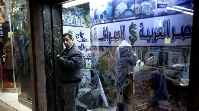 "An Egyptian man leaves after changing foreign currency at a currency exchange office, Arabic reads, ""Arabian Egypt for Exchange,"" in Cairo, Egypt, Sunday, Jan. 6, 2013. Egypt swore in 10 new ministers on Sunday in a Cabinet shake-up aimed at improving the government's handling of the country's ailing economy ahead of talks this week with the International Monetary Fund over a badly needed $4.8 billion loan. (AP Photo/Nasser Nasser)"