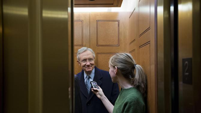 Senate Majority Leader Harry Reid, left, from Nevada, talks with a journalist as the elevator doors close as he departs the Capitol after a vote about the fiscal cliff, on Capitol Hill Tuesday, Jan. 1, 2013 in Washington. The Senate passed legislation early New Year's Day to neutralize a fiscal cliff combination of across-the-board tax increases and spending cuts that kicked in at midnight. (AP Photo/Alex Brandon)