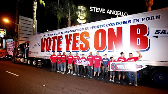 IMAGE DISTRIBUTED FOR AIDS Healthcare Foundation - Supporters of Vote Yes on B in Los Angeles, the condoms in porn measure on the November ballot led by AIDS Healthcare Foundation, hand out voter information and free condoms on L.A's famed Sunset Strip on Saturday, Oct. 27, 2012, in Los Angeles, Calif.  After an all day caravan to five cities throughout Los Angeles. The 'Yes on B' caravan covered 137 miles through Hollywood, Long Beach, Northridge, Canoga Park and West Hollywood handing out 150,000 condoms with only ten days before election day. (Photo by Joe Kohen/AP Images for AIDS Healthcare Foundation)