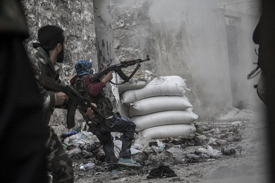 In this Wednesday, Oct. 24, 2012 photo, a rebel fighter retreats for cover as enemy fire targets the rebel position during clashes at the Moaskar front line, one of the battlefields in the Karmal Jabl neighborhood, of Aleppo, Syria. (AP Photo/Narciso Contreras).