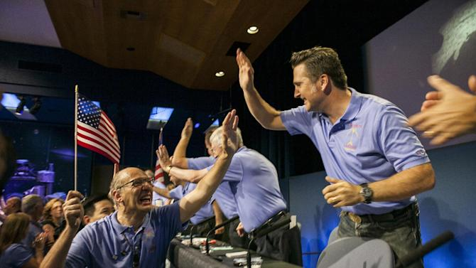 Mars Science Laboratory Curiosity team member Miguel San Martin, Chief Engineer, Guidance, Navigation, and Control at Jet Propulsion Laboratory, left, celebrates with Adam Steltzner, MSL entry, descent and landing (EDL) of the Mars Science Laboratory (MSL), right, after the successful landing of Curiosity rover on the surface of Mars at NASA's Jet Propulsion Laboratory in Pasadena, Calif., Sunday, Aug. 5, 2012. (AP Photo/Damian Dovarganes)
