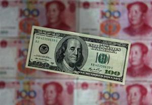 A photo illustration shows a $100 banknote placed above Chinese 100 yuan banknotes in Beijing