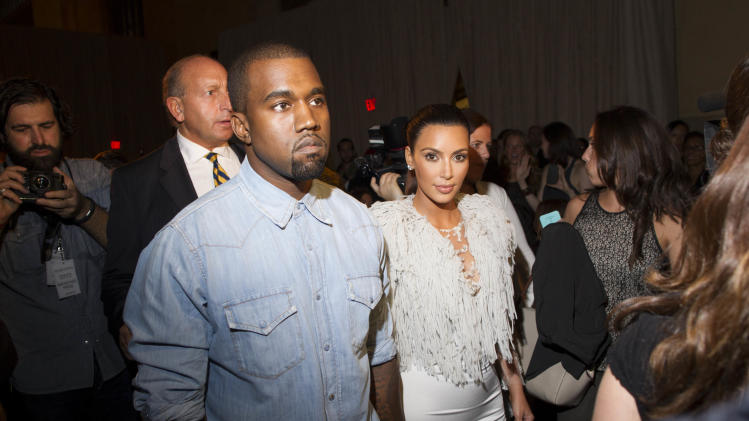 IMAGE DISTRIBUTED FOR FIJI WATER - Kanye West, left, and Kim Kardashian  attend the FIJI Water-sponsored Marchesa Spring 2013 Fashion Show at Vanderbilt Hall on Wednesday Sept. 12, 2012, in New York. (Photo by Victoria Will/Invision for FIJI Water /AP Images)