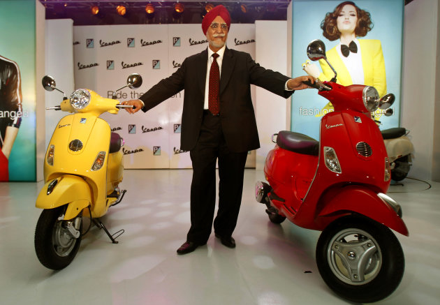 Chairman and Managing Director of Piaggio Vehicles Limited India Ravi Chopra poses with Vespa scooters during their launch in Mumbai, India, Thursday, April 26, 2012. The Italian company hopes to carve out a market for luxury scooters in one of the most cost-conscious markets in the world. The Vespa LX will cost around 66,661 rupees ($1,282) in India, a 40 percent premium to most scooters, but still the lowest sticker price in the world. (AP Photo/Rafiq Maqbool)
