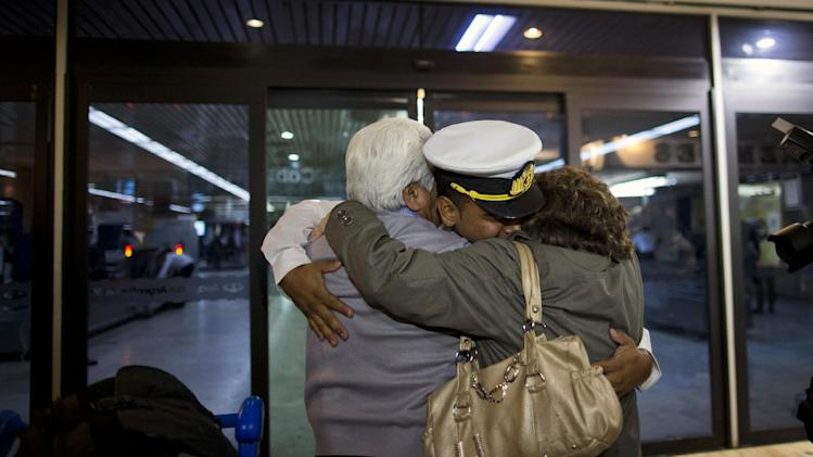 An Argentine sailor greets relatives as he arrives in Buenos Aires airport, Argentina, Thursday, Oct. 25, 2012. Nearly 300 navy cadets arrived to Argentina's capital from Ghana on an Air France charter hired by the government after Argentina's President Cristina Fernandez refused to negotiate the release of the Argentine naval sailing ship, Libertad. The ship had been held in a port outside Ghana's capital Oct. 2, when a Ghana court ruled to detain the vessel as collateral for Argentina's unpaid debts. (AP Photo/Natacha Pisarenko)