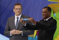 "Former Brazil soccer player Cafu holds the slip showing ""Brazil"" during the draw for the 2014 World Cup at the Costa do Sauipe resort in Sao Joao da Mata, Bahia state, December 6, 2013. REUTERS/Ricardo Moraes"