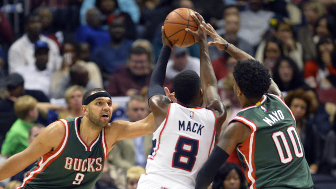 Milwaukee Bucks' Jared Dudley (9) and O.J. Mayo (00) guard Atlanta Hawks' Shelvin Mack (8) during the second half of an NBA basketball game Friday, Dec. 26, 2014, in Atlanta. Milwaukee won 107-77. (AP Photo/David Tulis)