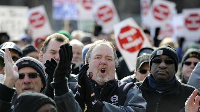 FILE - In a Tuesday, March 8, 2011 file photo, potestors stand outside the state Capitol in Lansing, Mich. objecting to proposed legislation that would authorize emergency financial managers to throw out union contracts. Unions are supporting a 2012 ballot initiative that would put collective bargaining rights in the state constitution. (AP Photo/The Detroit News, David Coates, File)  MANDATORY CREDIT