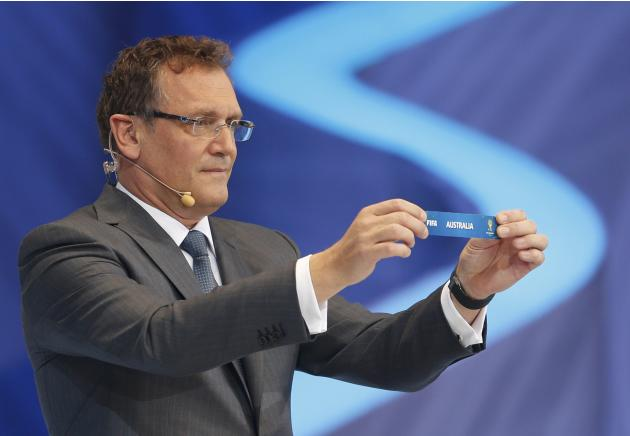 "Valcke holds up the slip showing ""Australia"" during the draw for the 2014 World Cup in Sao Joao da Mata"
