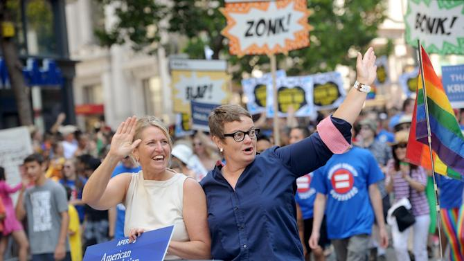 Proposition 8 plaintiffs Kris Perry, left, and Sandy Steir ride in San Francisco's 43rd annual gay pride parade Sunday, June 30, 2013. The couple wed on Friday after a U.S. Supreme Court decision cleared the way for same-sex marriages in California. (AP Photo/Noah Berger)