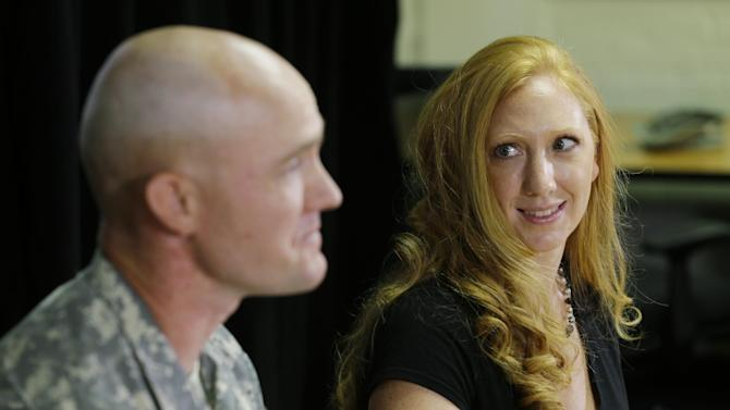 Shannon Carter, right, looks at her husband, U.S. Army Staff Sgt. Ty Carter, left, as he talks to reporters, Monday, July 29, 2013, at Joint Base Lewis-McChord in Washington state. Ty Carter will be awarded the Medal of Honor in August for his actions during a 2009 battle at a mountain outpost in Afghanistan where U.S. troops were far outnumbered. (AP Photo/Ted S. Warren)