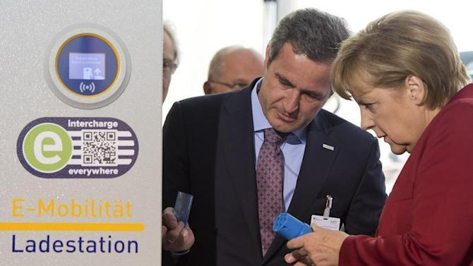 EnBW AG CEO Mastiaux explains the operation of an electric car charging booth to German Chancellor Merkel at the Electric Mobility Conference of German government in Berlin