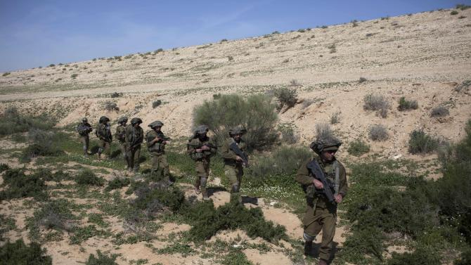 Israeli soldiers walk as they participate in a drill near Revivim southern Israel, Thursday, March 7, 2013. On a dusty field in Israel's southern desert, the military is gearing up for the next battle against a familiar foe: Hezbollah guerrillas in Lebanon. As the Syrian civil war intensifies on Israel's northern doorstep, military planners are growing increasingly jittery that the fighting could spill over into Israel, potentially dragging Hezbollah into the fray. (AP Photo/Sebastian Scheiner)