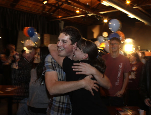 People attending an Amendment 64 watch party in a bar hug after a local television station announced the marijuana amendment's passage, in Denver, Colo., Tuesday, Nov. 6, 2012. The amendment would mak