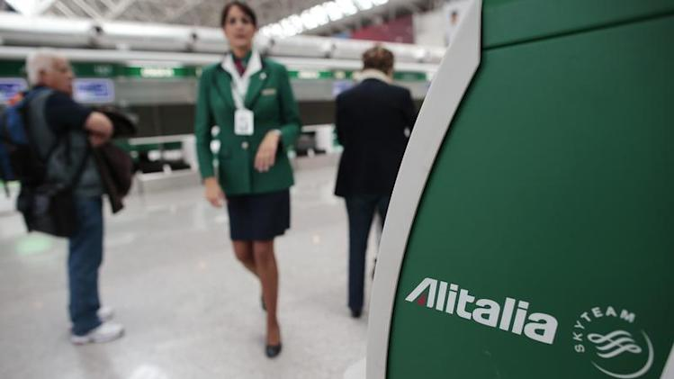 An Alitalia worker walks near an Alitalia auto check-in machine at Fiumicino airport in Rome