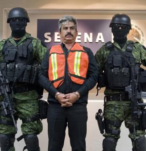 **  CORRECTS CAPTION TO REMOVE THE LAST TWO SENTENCES AND THE SECOND BYLINE  **   Saul Solis Solis, center, alleged member of Mexico's Knights Templar drug cartel, is escorted by soldiers during his presentation to the media in Mexico City, Tuesday, Sept. 20, 2011. Solis Solis, a former police chief and one-time congressional candidate, was captured Monday in the cartel's home state of Michoacan, Mexico. (AP Photo/str)
