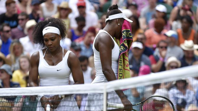Venus Williams of the U.S.A. wipes her face as Serena Williams of the U.S.A. looks on during their match at the Wimbledon Tennis Championships in London