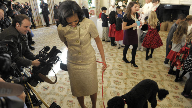 First lady Michelle Obama, accompanied by first dog Bo, walks past reporters during a visit to the State Dining Room of the White House in Washington, Wednesday, Nov. 28, 2012, during a preview of the White House holiday decorations. The theme for the White House Christmas 2012 is Joy to All. School children were also in the State Dining Room decorating holiday treats. (AP Photo/Susan Walsh)
