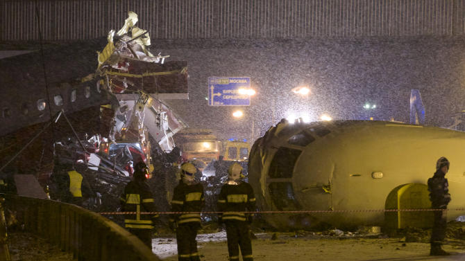 Rescuers work at the site where a plane careered off the runway at Vnukovo Airport in Moscow, Saturday, Dec. 29, 2012. A Tu-204 aircraft belonging to Russian airline Red Wings careered off the runway at Russia's third-busiest airport on Saturday, broke into pieces and caught fire, killing several people. (AP Photo/Ivan Sekretarev)