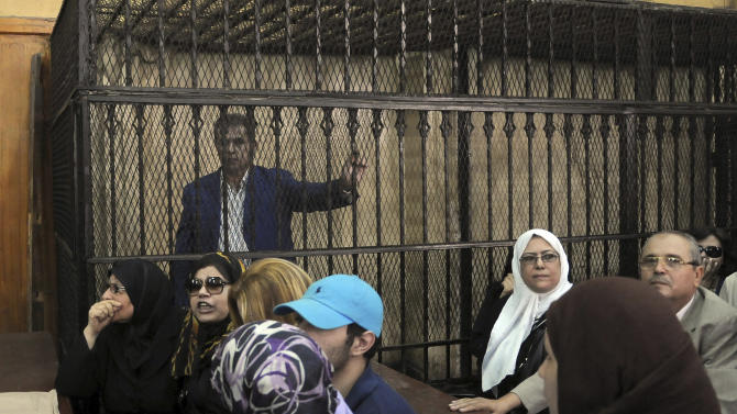 "Tawfiq Okasha, a popular Egyptian TV presenter accused of inciting the killing of the country's new president on air, stands in the defendants cage at the opening of his trial, in Cairo, Egypt, Saturday Sept. 1, 2012. Egypt's state news agency said the prosecutor accused Okasha of using his TV program in July and August to incite the killing of President Mohammed Morsi, and of insulting him by calling him an ""illegitimate leader and a liar."" (AP Photo/Mohammed Assad)"