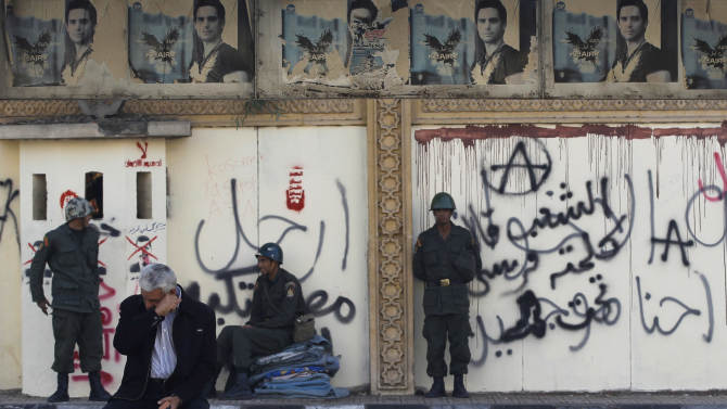 """A man sits on a bench as soldiers guard the presidential palace in Cairo, Egypt, Thursday, Dec. 13, 2012. Egypt's opposition called on its followers to vote """"no"""" in a crucial referendum on a disputed constitution drafted by Islamist supporters of President Mohammed Morsi. (AP Photo/Petr David Josek)"""