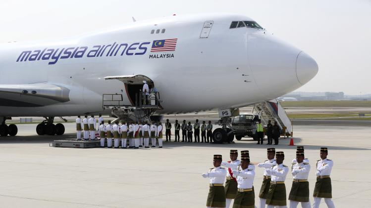 The remains of victims of the MH17 disaster are carried from a plane during a repatriation ceremony at the Bunga Raya complex of KLIA airport in Sepang