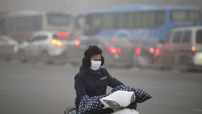 A man wearing a mask rides his electric bicycle along a street on a smoggy day in Zhengzhou