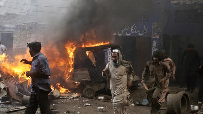 Pakistani men, part of an angry mob, run after burning belongings of Christian families, in Lahore, Pakistan, Saturday, March 9, 2013. A mob of hundreds of people in the eastern Pakistani city of Lahore attacked a Christian neighborhood Saturday and set fire to homes after hearing accusations that a Christian man had committed blasphemy against Islam's prophet, said a police officer. (AP Photo/K.M. Chaudary)