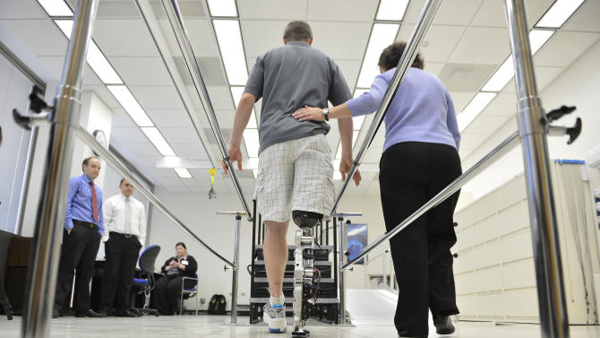 "Physical therapist assistant Suzanne Finucane, right, helps Zac Vawter as he practices walking with an experimental ""bionic"" leg at the Rehabilitation Institute of Chicago, Thursday, Oct. 25, 2012 in Chicago.  Vawter will put his bionic leg to the ultimate test Sunday, Nov. 4,  when he attempts to climb 103 flights of stairs to the top of Chicago's Willis Tower, one of the world's tallest skyscrapers. If all goes well, he'll make history with the bionic leg's public debut.  (AP Photo/Brian Kersey)"