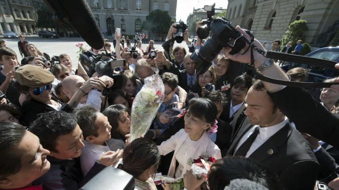 Myanmar opposition leader Aung San Suu Kyi, center, is surrounded by media and residents after her visit to the government building in Bern, Switzerland, Friday, June 15, 2012. The European trip is seen as a sign of gratitude to governments and organizations that supported Suu Kyi's peaceful struggle against Myanmar's former military rulers over more than two decades, 15 years of which she spent under house arrest. (AP Photo/Lukas Lehmann)