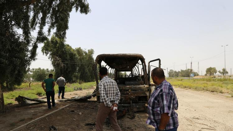 People look at a burnt bus in Taji, north of Baghdad