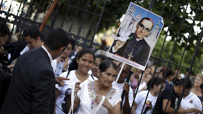 People walks with a picture of the late Archbishop Oscar Arnulfo Romero towards his grave at the National Cathedral in San Salvador
