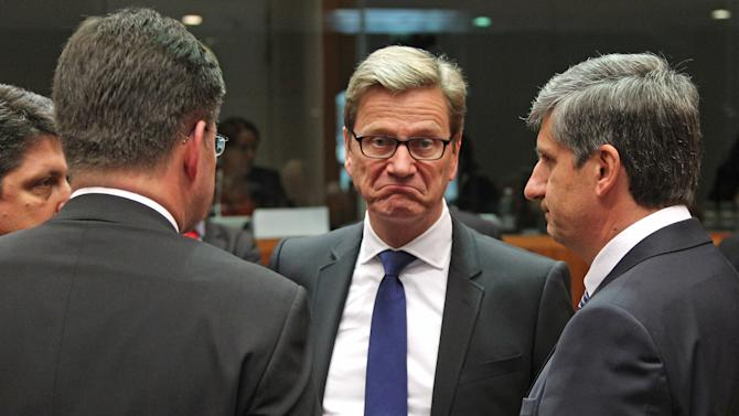 German Foreign Minister Guido Westerwelle, center, listens to Austrian Foreign Minister Michael Spindelegger, right, and other counterparts, during the EU foreign ministers meeting, at the European Council building in Brussels, Monday, May 27, 2013. The European Union nations remain divided on Monday whether to ease sanctions against Syria to allow for weapons shipments to rebels fighting the regime of Syria's President Bashar Assad. (AP Photo/Yves Logghe)