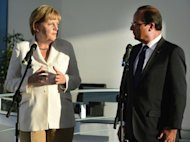 German Chancellor Angela Merkel and French President Francois Hollande address a press conference at the chancellery in Berlin. She urged Greece to stick to its programme of reforms