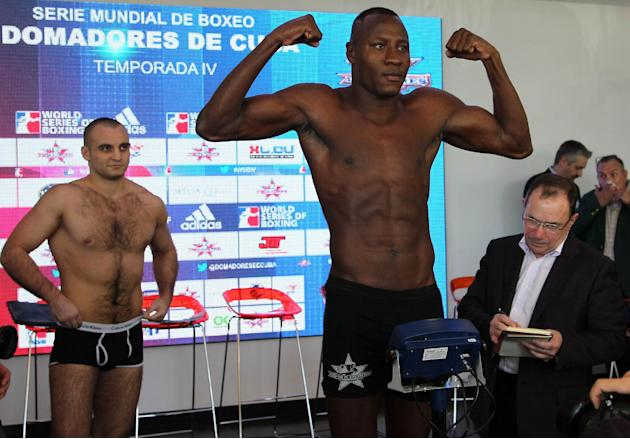 CORRECTS DAY OF BOXING MATCHES Cuban heavyweight boxer Erislandy Savon, at front right, poses for photos during the weigh-in session as his opponent Vitaly Kudukhov from Russia, left, looks on in  Hav