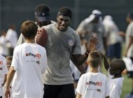Jacksonville Jaguars rookie wide receiver Justin Blackmon greets kids at an NFL football Play 60 youth clinic at the Cleveland Browns training facility in Berea, Ohio Friday, June 29, 2012. (AP Photo/Mark Duncan)